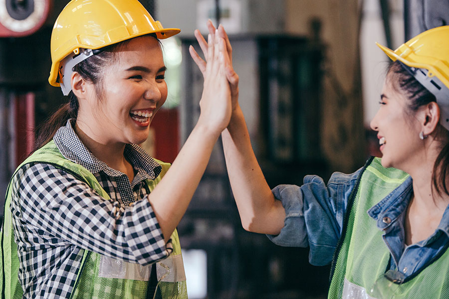 AccuComp - Two Smiling Warehouse Workers Giving Eachother High Five at Work