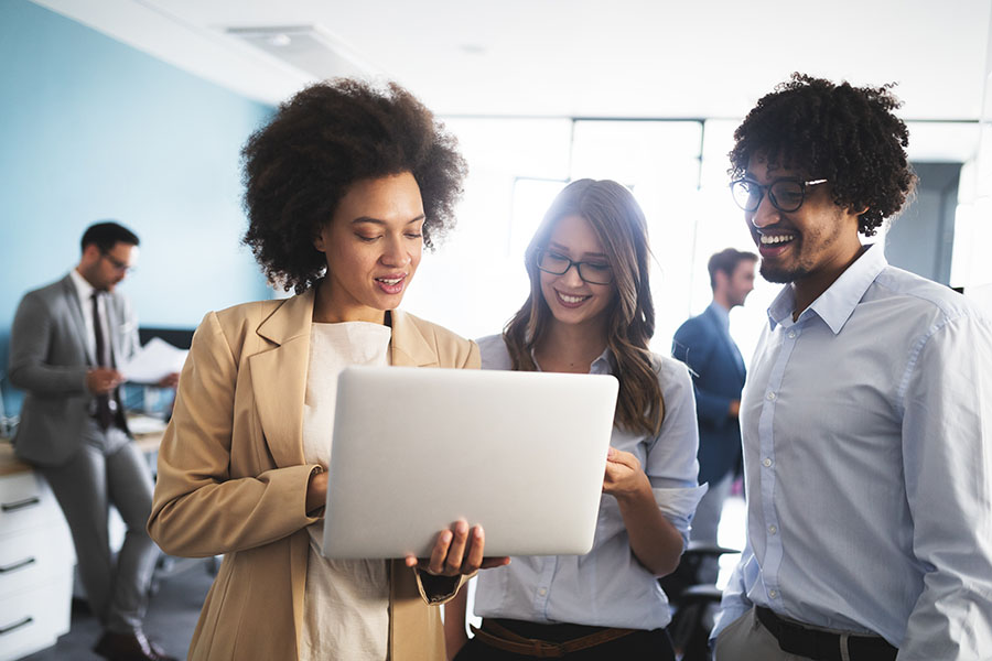 Employee Benefits - Group of Happy Employees Standing in the Office Looking at a Laptop